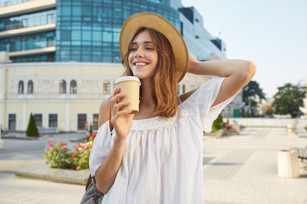 Das porträt im freien der fröhlichen charmanten jungen frau trägt einen stilvollen sommerhut und ein weißes kleid, fühlt sich entspannt, steht und trinkt kaffee zum mitnehmen auf der straße in der stadt Kostenlose Fotos