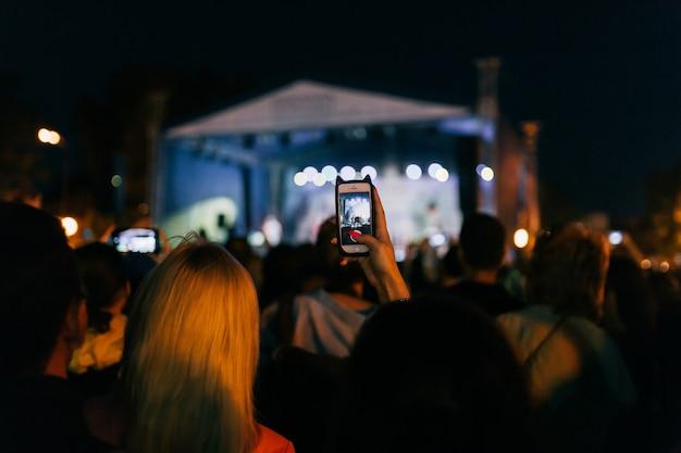 Das publikum nimmt videos auf und fotografiert die band im konzert auf dem handy Premium Fotos