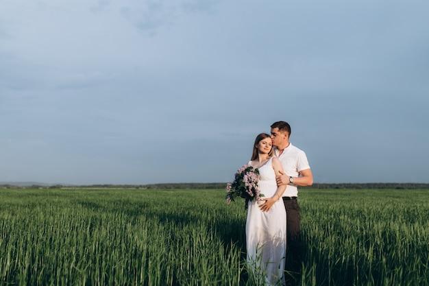 Das reizende paar in der liebe, die blumenstrauß umfasst und hält Kostenlose Fotos