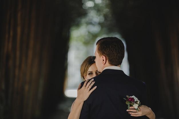 Das reizende paar in der liebe, die im wald umfasst Kostenlose Fotos