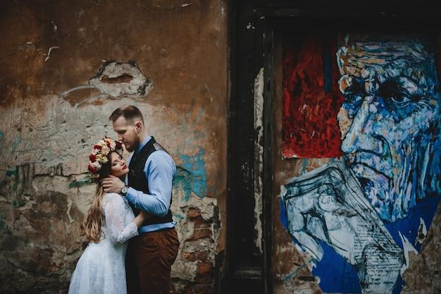 Das reizende paar in der liebe, die nahe wand umfasst Kostenlose Fotos