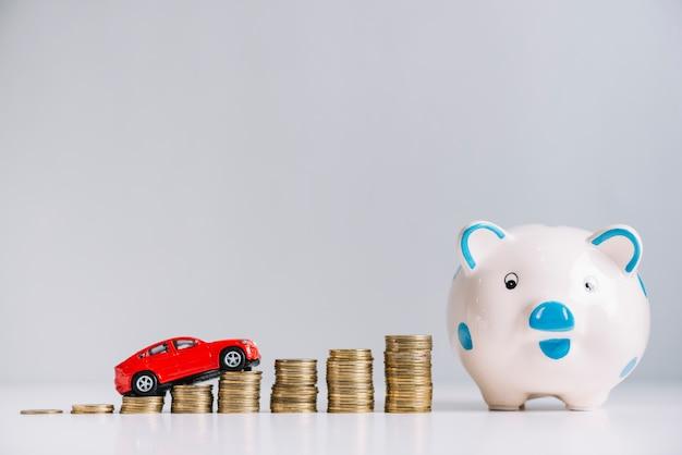 Das rote auto, das über das erhöhen der gestapelten münzen fährt, nähern sich piggybank Kostenlose Fotos