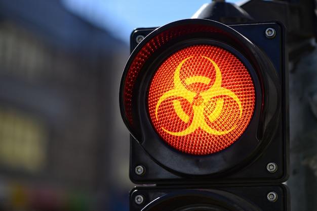 Das rote semaphorlicht mit biohazard-warnsymbol, covid-19-containment-konzept Premium Fotos