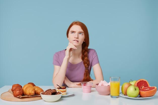 Das rothaarige mädchen, das nach oben schaut und darüber nachdenkt, was es zum frühstück essen soll, sitzt an einem tisch, auf dem backwaren und frisches obst liegen Kostenlose Fotos