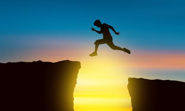 Das schattenbild eines mannes, der über den abgrund zum zeitpunkt des sonnensatzes, des konzeptes des sieges und des erfolgs springt Premium Fotos