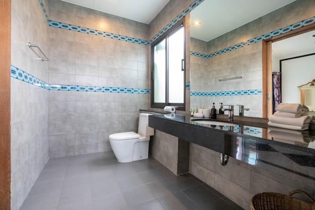 Das schöne badezimmer verfügt über ein waschbecken, eine wc-schüssel im haus oder ein wohngebäude Premium Fotos