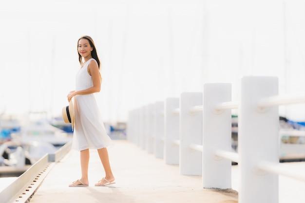 Das schöne junge asiatische frauenfreizeitlächeln des porträts, das glücklich ist, entspannen sich um yachthafen Kostenlose Fotos