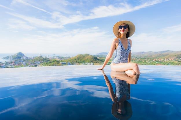 Das schöne junge asiatische frauenlächeln des porträts, das glücklich ist, entspannen sich um swimmingpool im hotelerholungsort für freizeit Kostenlose Fotos