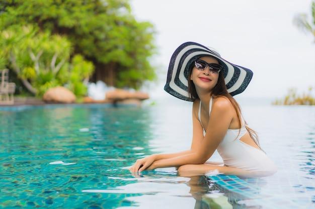 Das schöne junge asiatische frauenlächeln des porträts, das glücklich ist, entspannen sich um swimmingpool im hotelerholungsort Kostenlose Fotos
