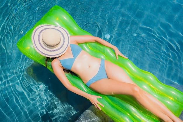 Das schöne junge asiatische frauenlächeln des porträts, das glücklich ist, entspannen sich und freizeit im swimmingpool Kostenlose Fotos