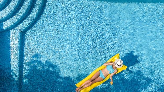 Das schöne junge mädchen, das im swimmingpool sich entspannt, schwimmt auf aufblasbarer matratze und hat spaß im wasser auf familienurlaub, tropisches ferienzentrum, luftbrummenansicht von oben Premium Fotos