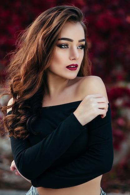 Das schöne Mädchen steht in der Nähe von Wall mit Blättern ...