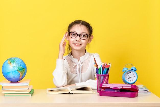Das schulmädchen sitzt am schreibtisch und hebt die hand, um eine antwort zu erhalten. zurück zur schule. das neue schuljahr. konzept der kindererziehung. speicherplatz kopieren Premium Fotos