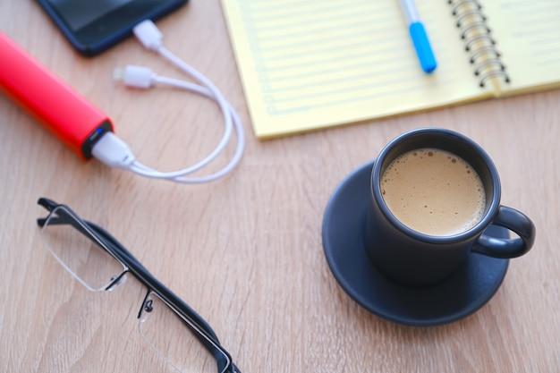 Das smartphone wird von der poverbank geladen. tasse kaffee, tagebuch, bleistift und gläser auf dem tisch Premium Fotos