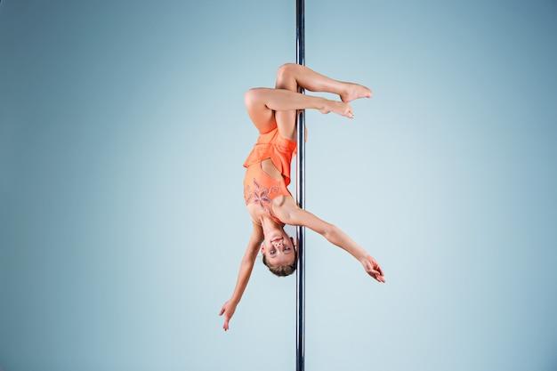 Das starke und anmutige junge mädchen, das akrobatische übungen auf pylon durchführt Kostenlose Fotos