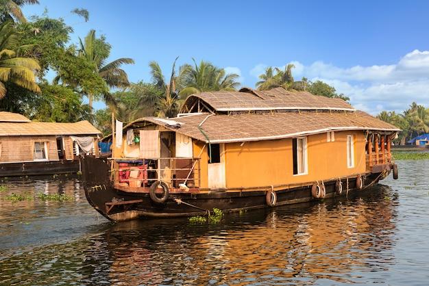 Das traditionelle hausboot liegt an den ufern eines fischteichs in indien. Premium Fotos