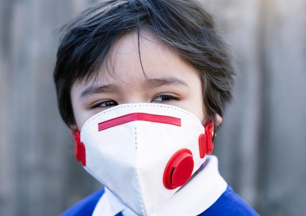 Das tragende gesicht des nahaufnahme-kindergesichtes schützt gesichtsmaske für pullution oder virus Premium Fotos
