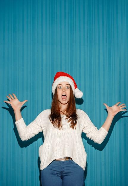 Das überraschte weihnachtsmädchen, das eine weihnachtsmütze auf dem blauen hintergrund trägt Kostenlose Fotos
