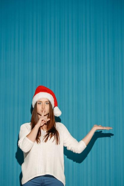 Das überraschte weihnachtsmädchen, das eine weihnachtsmütze trägt, zeigt rechts auf dem blauen hintergrund Kostenlose Fotos