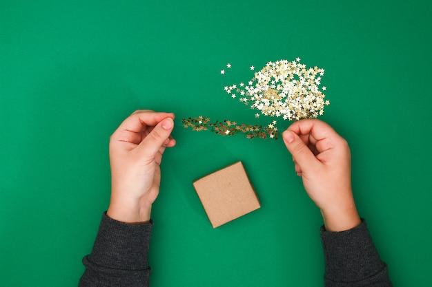 Das ursprüngliche design eines weihnachtsgeschenks aus kraftpapier, scotch und konfetti aus goldsternen Premium Fotos