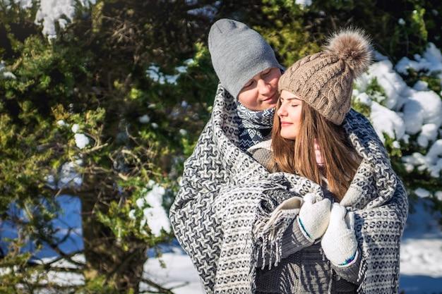 Das verliebte paar, das mit decke bedeckt wird, umarmt im winterwald Premium Fotos