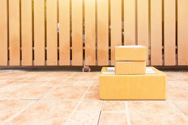 Das warenpaket und an den empfänger zu hause gesendet, lieferbote hält kisten person, die die paketbox an den empfänger gesendet hat, um zu hause anzukommen Premium Fotos