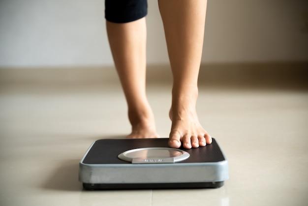 Das weibliche bein, das ein tritt, wiegen skalen. gesundes lebensstil-, lebensmittel- und sportkonzept. Premium Fotos