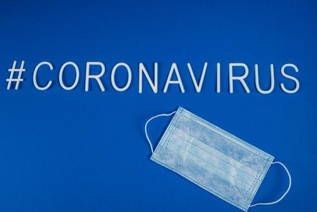 Das wort coronavirus mit weißen buchstaben gelegt. atemschutzmaske neben dem wort coronavirus. nachrichten in sozialen netzwerken. hashtag. flache lage, copyspace Premium Fotos