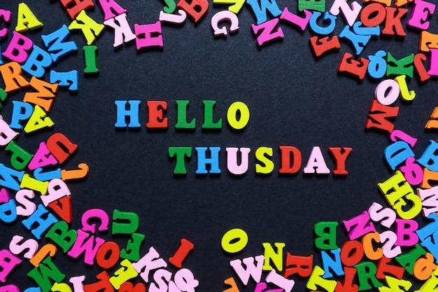 Das wort hallo donnerstag aus bunten holzbuchstaben auf einem schwarzen hintergrund Premium Fotos