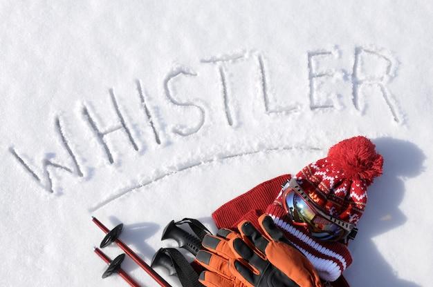 Das wort pfeifer geschrieben in schnee mit skistöcken, schutzbrillen und hüten Kostenlose Fotos