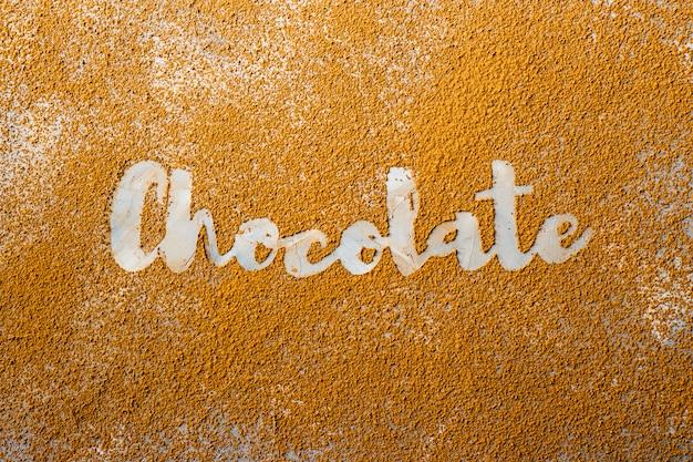 Das wort schokolade wird in weiß auf dem hintergrund von kakaopulver gedruckt Premium Fotos
