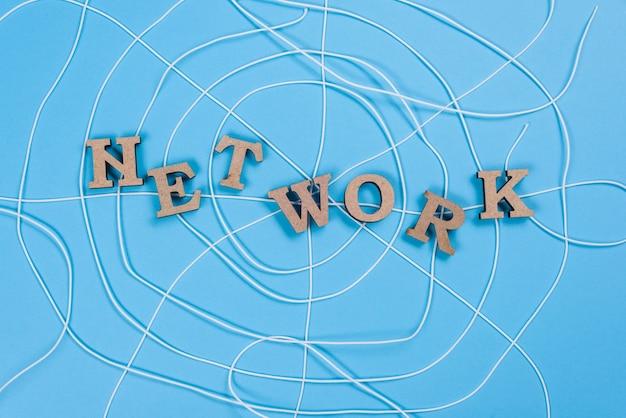 Das wortnetz mit hölzernen buchstaben in form eines abstrakten spinnennetzes, blauer hintergrund Premium Fotos