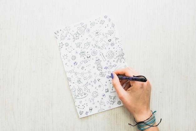 Das zeichnungsgekritzel der weiblichen künstlerhand mit stift auf papier über hölzernem strukturiertem Kostenlose Fotos