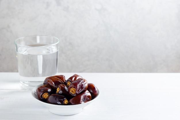 Daten und ein glas wasser auf weißem holztisch - ramadan, iftar-lebensmittel. Premium Fotos