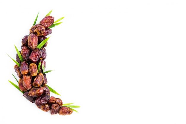 Datteln palmenfrucht angeordnet in form des halbmondes. ramadan kareem. Premium Fotos