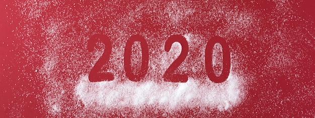Datum des guten rutsch ins neue jahr 2020 mit schneefällen auf rot Premium Fotos