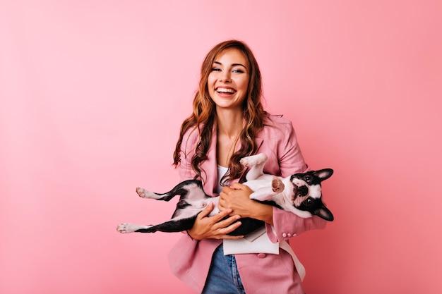 Debonair junge frau in der stilvollen jacke, die lustige französische bulldogge hält. porträt des scherzhaften langhaarigen mädchens, das zeit mit ihrem hund verbringt. Kostenlose Fotos