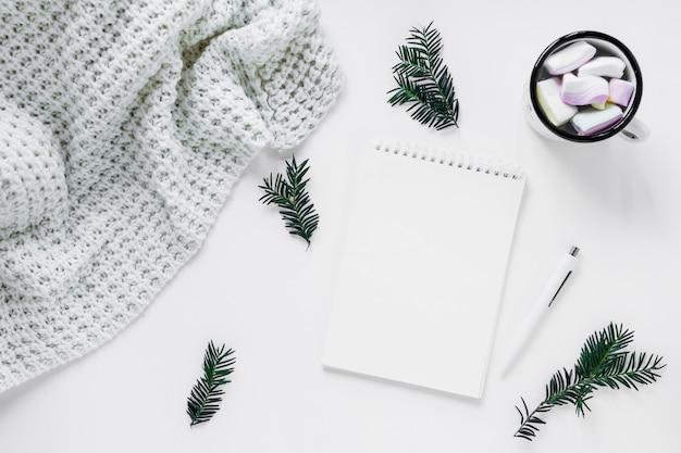 Decke und heiße schokolade nahe den nadelbaumzweigen und -notizbuch Kostenlose Fotos