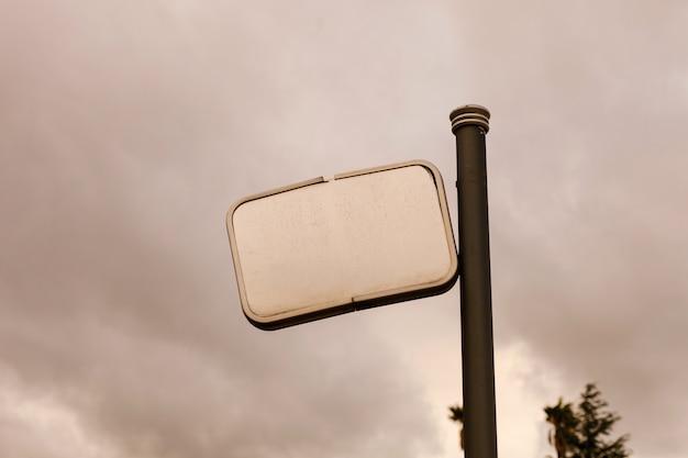 Defektes leeres plakat mit einem grauen himmelhintergrund Premium Fotos
