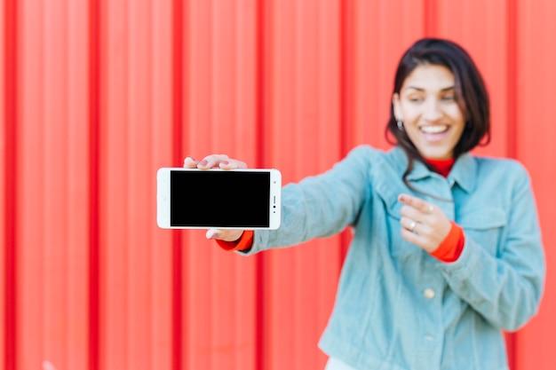 Defocused lächelnde frau, die handy zeigt Kostenlose Fotos