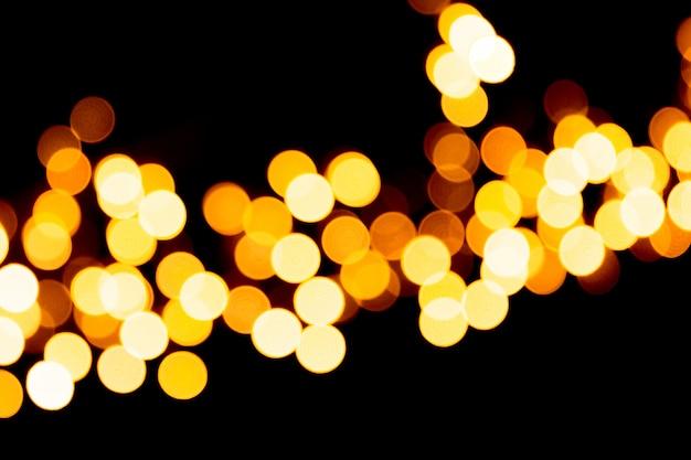 Defocused stadtgoldnacht-bokeh zusammenfassungshintergrund. verschwommen viele runde gelbes licht auf dunklem hintergrund Premium Fotos