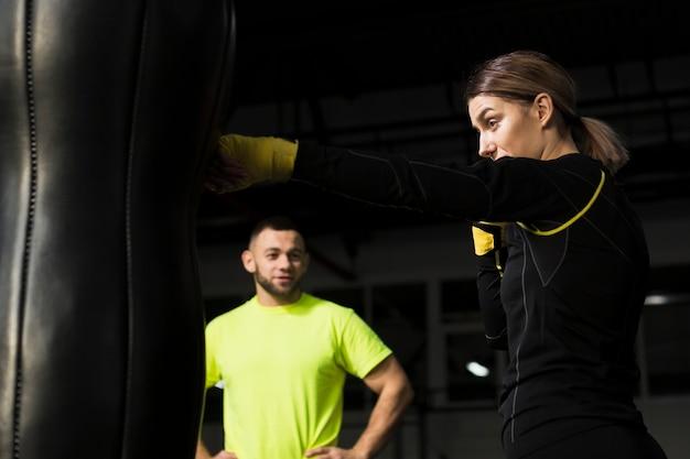 Defocused trainer, der weiblichen boxer aufpasst, auf sandsack zu üben Kostenlose Fotos