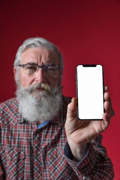 Defocussed älterer mann, der handy mit leerem weißem schirm gegen roten hintergrund zeigt Kostenlose Fotos