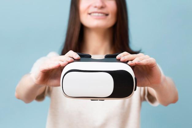 Defokussierte frau, die virtual-reality-headset hält Kostenlose Fotos
