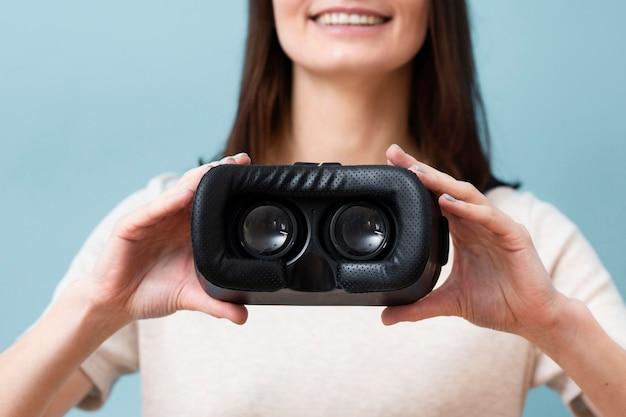 Defokussierte smiley-frau, die virtual-reality-headset hält Kostenlose Fotos