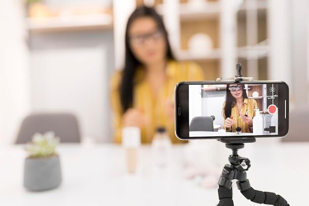 Defokussierte weibliche vloggerin zu hause mit smartphone Kostenlose Fotos