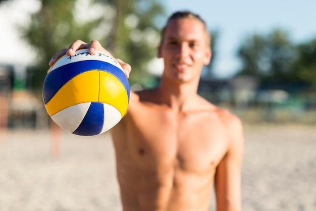 Defokussierter hemdloser männlicher volleyballspieler am strand, der ball hält Kostenlose Fotos