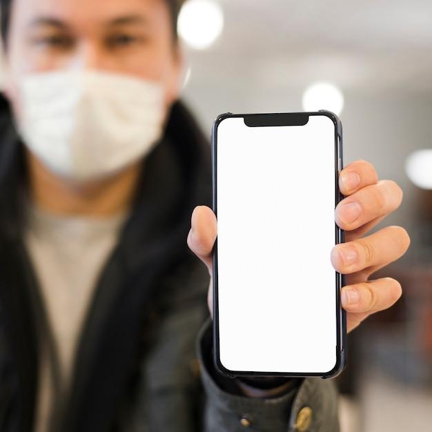 Defokussierter mann mit der medizinischen maske, die telefon hält Kostenlose Fotos
