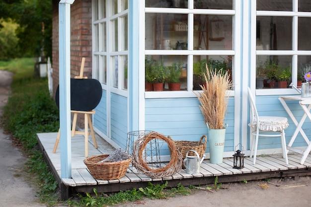 Dekor des hofes des landhauses. grüne pflanzen und blumen auf terrassenhaus. weidenkörbe Premium Fotos
