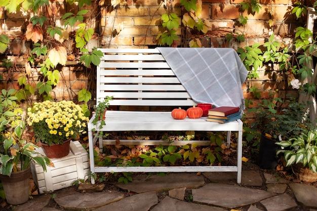 Dekor herbsthof. weiße bank im herbstgarten mit pflanzen und chrysantheme Premium Fotos